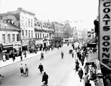 Photograph of Yonge Street, Toronto, showing stores and other buildings, with people walking on the sidewalks and in the street, during the Hurricane Hazel relief campaign, 1954