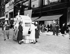 Photograph of a woman dropping a donation into a Hurricane Hazel relief booth while members of the Salvation Army look on, Toronto, 1954