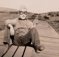Photograph of a young man (Gordon McLean) riding on the top of a boxcar