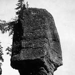 Photograph of a man in front of a rock formation, Hopewell, New Brunswick, date unknown